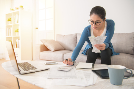 Foto de mixed race asian chinese housewife calculating accounting new year budget holding a receipt using calculator sitting on sofa in the living room at home - Imagen libre de derechos