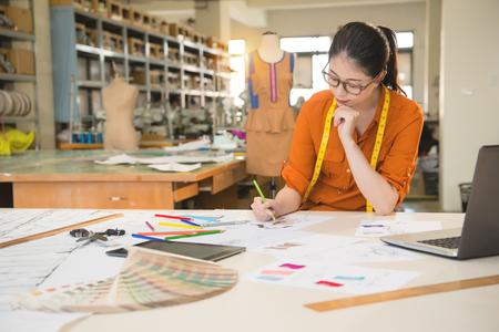 Photo pour authentic image of asian fashion woman designer drawing design sketch working in her manufacturing office studio. profession and job occupation concept. - image libre de droit