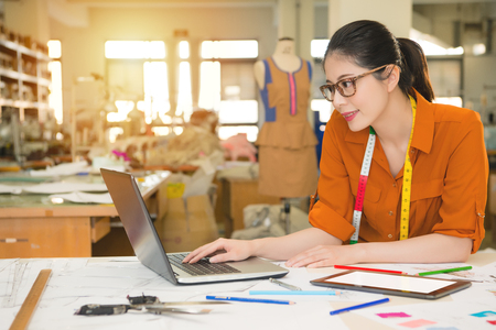 Photo for young beauty happy young fashion asian designer using computer laptop research on internet for new season trend in manufacturing office studio. profession and job occupation concept. - Royalty Free Image