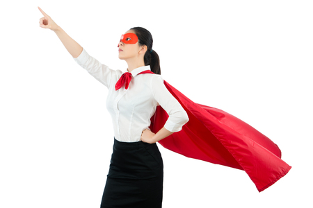 Foto de a young lady is dressed up as a superhero and pointing up with a red mask and cape with formal shirt isolated on white background over copyspace. strength and powerful concept. - Imagen libre de derechos