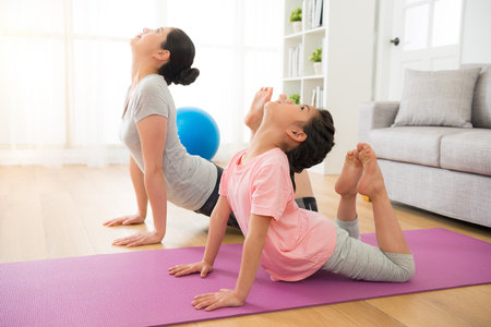Photo pour asian mother and daughter doing yoga exercises on vacation in the room at home. people having fun indoors with fitness. concept of friendly family and of summer day. - image libre de droit