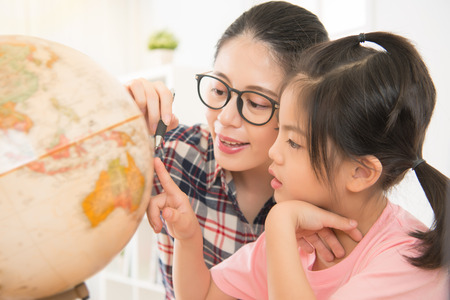 Photo for pretty homeschooling mother happy teaching smart daughter private lessons in globe. asia seriously girl children touch map and curious watching. - Royalty Free Image