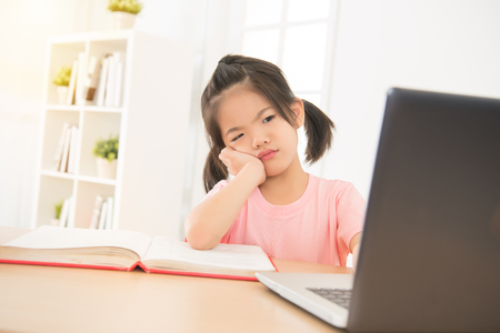 Photo pour cute asian little daughter girl looking confused and hand hold on chin in front of laptop computer at afternoon in the room. kid study concept. - image libre de droit