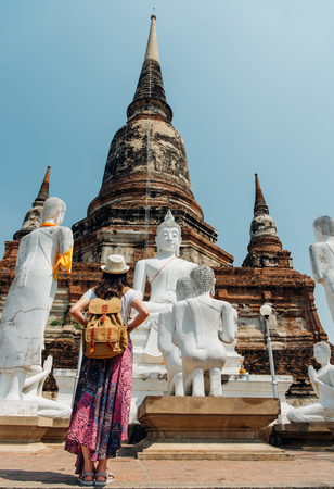 Photo for Young girl tourist from behind looking at statue view of Wat Yai Chai Mongkhon of Thailand at famous Ayutthaya tourism attraction during travel vacation in Bangkok. Asia summer holiday vacation. - Royalty Free Image