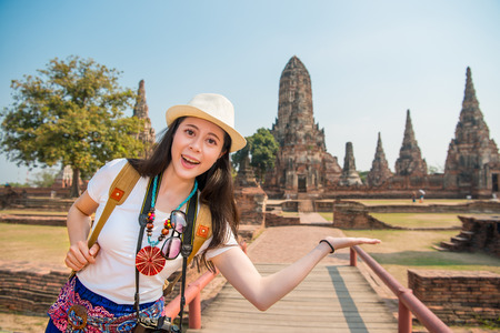 Photo for Backpacker asian woman smiling happy and do presenting gesture in front of famous tourist destination in Wat chaiwatthanaram temple of ayutthaya, thailand. Copy space. - Royalty Free Image
