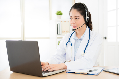Foto de female doctor through internet conversation while looking at computer in hospital with patient and typing all content record in the computer data files medical insurance. - Imagen libre de derechos