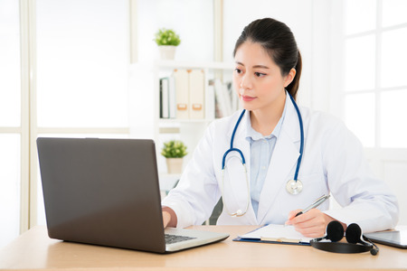 Foto de professional doctor seriously searching medical records about new patient through online medicine system and writing note on the paper board research treatment method. - Imagen libre de derechos