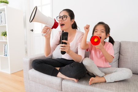 Photo pour young mom and daughter through megaphone watching the sports channel broadcast sports game to help support the team cheer up hope to win the game win at home on the couch. - image libre de droit