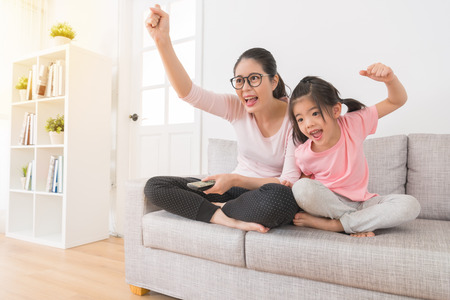 Photo pour happy woman with children watching TV sports channel favorite football team winning was excited to hands fist gesture to celebrate victory on the sofa in the family lounge. - image libre de droit