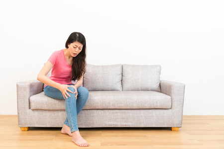 Photo for young beautiful woman feeling knee pain after sport movement was injured sitting on sofa in the living room to resting in wooden floor with white background. - Royalty Free Image