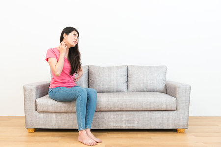 Foto de young attractive woman having allergy problem feeling body itchy sitting on sofa and looking at white background using hand scratching to soothing in wooden floor. - Imagen libre de derechos