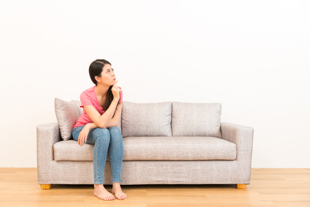 Photo pour woman sitting on the couch looking and thinking pose on wooden floor with white wall background. - image libre de droit