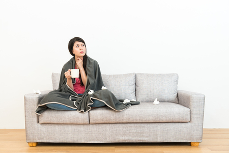 Photo for unhappy pretty lady catching a cold feeling throat painful drinking hot water and sitting on sofa couch looking at white background with wooden floor. - Royalty Free Image