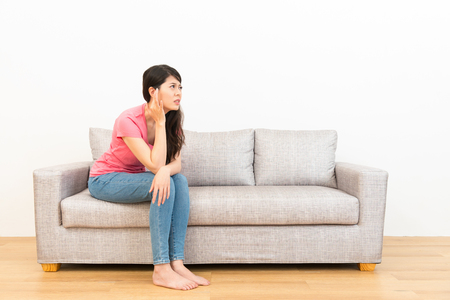 Photo for young woman crushed ear painful position sitting on couch looked at white background with wood floor at home in living room. - Royalty Free Image