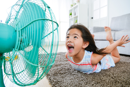 Foto de sweet beautiful little children lying down on living room floor and face to electric fan enjoying cool wind with flying posing with selective focus photo. - Imagen libre de derechos