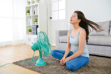 Photo pour beauty young woman sitting on living room and using electric fan enjoying cool wind for eliminating summer season heat at home. - image libre de droit
