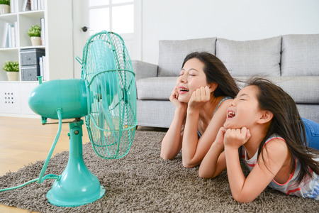 Photo for pleasantly mother with young little daughter lying down on living room floor and face to electric fan enjoying blowing cool wind together at summer. - Royalty Free Image
