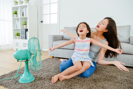 Photo pour happy little girl sitting on young mother legs and enjoying electric fan comfortable cool wind together at summer season in living room. - image libre de droit