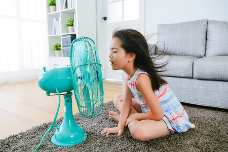 Foto de lovely youth little girl sitting on living room floor playing electric fan and enjoying cool wind in summer season at home. - Imagen libre de derechos