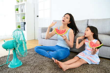 Photo pour pretty mother with cute little daughter feeling very hot at summer day and eating watermelon blowing electric fan cool wind. - image libre de droit