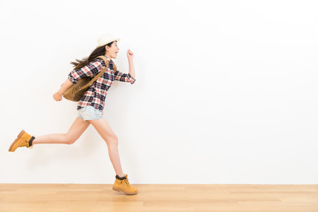 Photo pour happy asian traveler on the wooden floor showing performance of the posture of running excited going to blank copyspace with white wall background for travel advertising. - image libre de droit