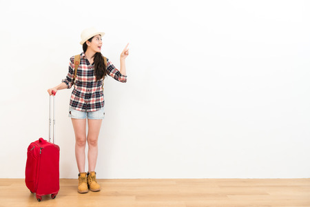 Photo pour happy smiling woman backpacker holding travel suitcase and pointing white background empty area standing on wooden floor. - image libre de droit
