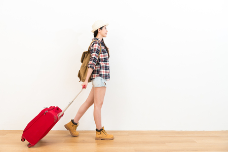 Photo for happy sweet backpacker lady planning going to travel and carrying personal suitcase walking on wooden floor with white wall background. - Royalty Free Image