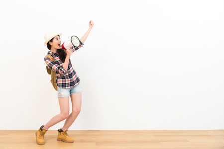 Photo pour happy cheerful woman looking at white background making victory winner celebrate gesture and using loudspeaker announced information on wooden floor. - image libre de droit