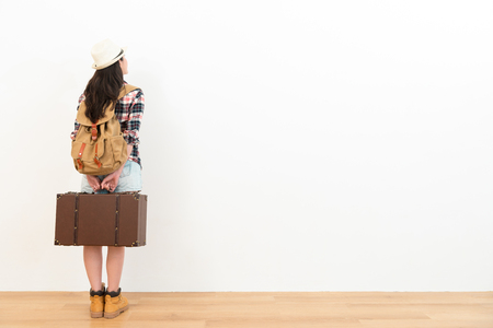 Foto de back view photo of pretty young traveler woman standing on wooden floor and holding retro suitcase looking at white wall background thinking about travel planning. - Imagen libre de derechos