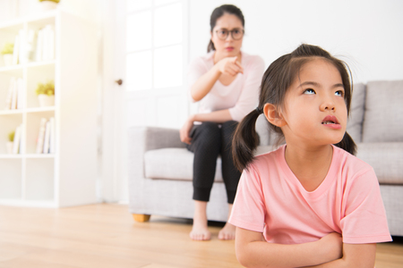 Foto de asian mother sitting on the back of the sofa angry pointing to the impatient and unhappy expression of the little girl seriously at home while children making mistake. - Imagen libre de derechos