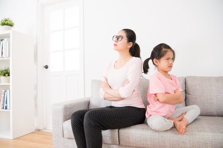 Foto de the young mother and the little daughter back to the back sitting on the sofa in the living room and each other to ignore each other after the quarrel feeling very angry. - Imagen libre de derechos