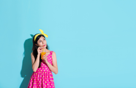 Photo pour beauty lovely woman thinking daydreaming isolated on blue background when she enjoying drinking cooling orange juice. - image libre de droit