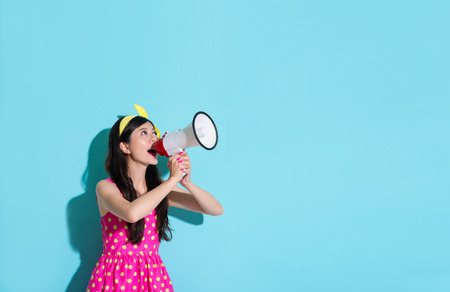 Photo pour happy beautiful woman using megaphone speaking information and wearing pink cute dress in blue wall background. - image libre de droit