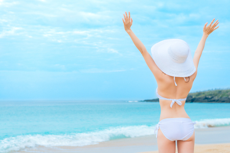 Foto de back view photo of young beauty girl wearing bikini clothing with hat standing on beach and opening arms enjoying seaside landscape. - Imagen libre de derechos