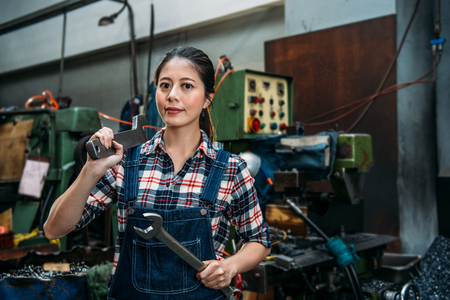 Foto de young industrial factory woman holding two large wrenches confident smiling face to camera standing in milling machine factory. - Imagen libre de derechos