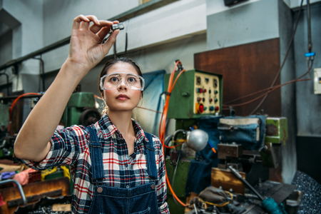 Foto de beautiful milling machine female staff wearing safety goggles focus on components finished product standing in front of technology machine. - Imagen libre de derechos