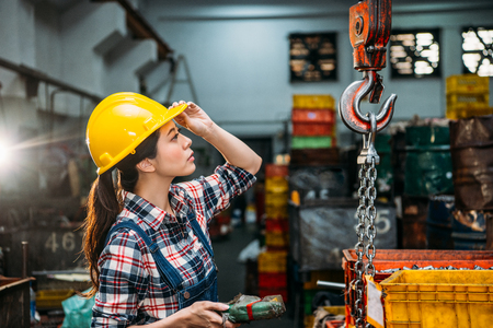Foto de seriously components factory female staff hold helmet focus on looking at chain cranes and through remote control  adjust for delivery finished products. - Imagen libre de derechos