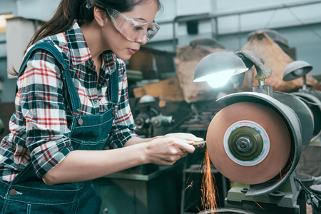 Foto de beauty pretty female lathe company employee wearing safety goggles to grind steel product and using abrasive disc machine working. - Imagen libre de derechos
