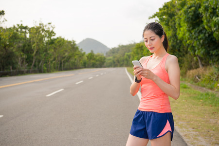 Photo pour beautiful female jogging runner wearing smartwatch standing on road street using mobile cell phone contact texting with friends after completion marathon game. - image libre de droit