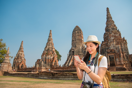 Photo pour Asian woman using smartphone searching looking map of Wat Chaiwatthanaram park in Ayutthaya, Thailand, texting sms message online on mobile smartphone for business over copyspace. - image libre de droit