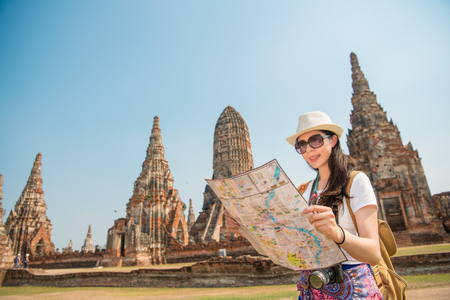 Foto de Asian tourist woman with map paper searching for attractions traveling in Ayutthaya town with the Wat Chaiwatthanaram in the background. Young chinese adult visiting the city in Thailand. - Imagen libre de derechos