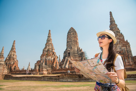 Foto de Travel in Thailand - Asian tourist woman with local map searching for directions with the Ayutthaya tour landscape in the background and thinking good things on the copyspace. - Imagen libre de derechos