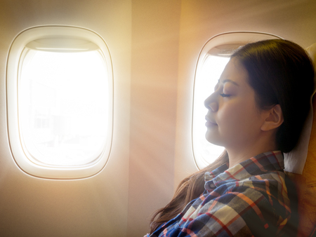 Foto de tired brunette casual asian lady napping on comfortable cabin seat while flying traveling with sunshiny from outside sky. - Imagen libre de derechos
