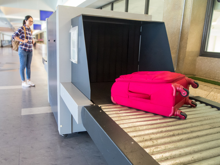Photo pour beautiful woman chinese waiting luggage through point of checking the scanner. Baggage X-ray machine band on the conveyor belt at the airport. - image libre de droit