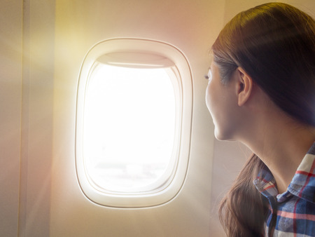 Photo pour traveler in the airplane. international exchange student sitting at the window of the plane look out sky glare when the plane flying. - image libre de droit