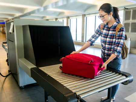 Foto de beautiful woman chinese put luggage at Point of checking the scanner. Baggage X-ray machine band on the conveyor belt at the airport. selective focus - Imagen libre de derechos