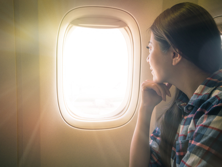 Foto de photo of sweet lady seriously view scenery of sunset sky. traveler sitting on the comfortable cabin seat looking out concept. - Imagen libre de derechos