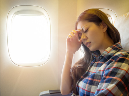 Foto de wearing casual style clothes lady take the plane feeling painful for head and hand putting on forehead express uncomfortable. - Imagen libre de derechos