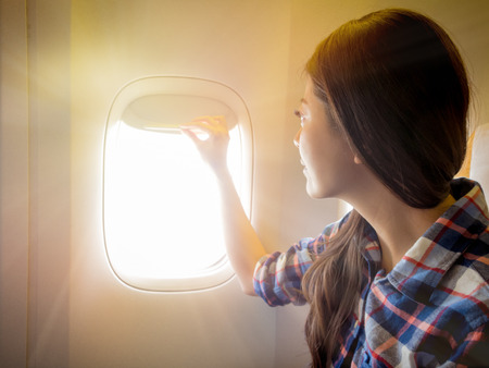 Foto de airplane takeoff and landing the window must open. smiling girl open watching outside landscape with sunny weather feeling pleasantly. - Imagen libre de derechos