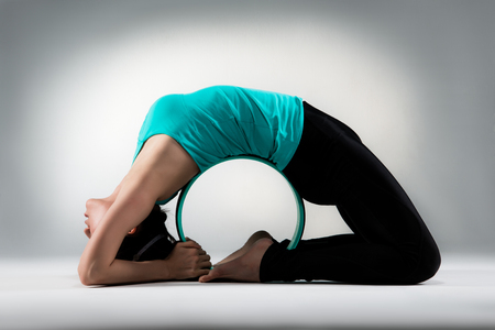 Foto de professional yoga lady back around pilates ring lying on gray background floor and showing perfect fitness posture in the studio. - Imagen libre de derechos